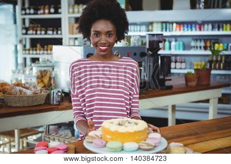 Portrait of smiling woman standing at counter in cafe