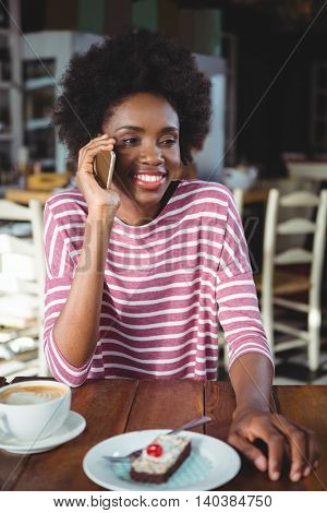 Smiling woman talking on the mobile phone while sitting in cafe