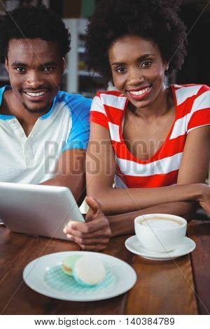 Portrait of smiling couple using digital tablet while having cup of coffee in cafe