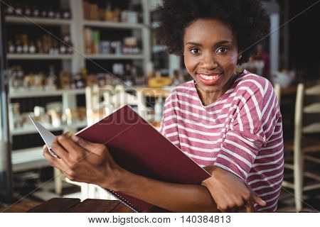 Portrait of smiling woman sitting in cafe reading menu