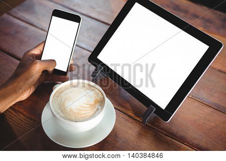 Woman using mobile phone and digital tablet while having cup of coffee in cafe