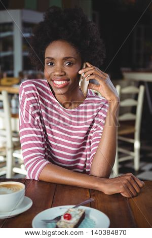 Portrait of smiling woman talking on the mobile phone while sitting in cafe