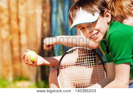 Portrait of smiling sportive ten years old boy in cap, waiting for the tennis match