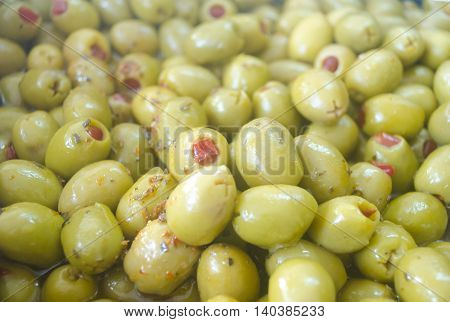 A heap of stuffed green olives. Olives background. Close up.