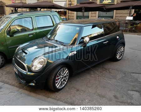 FLORENCE ITALY - CIRCA APRIL 2016: dark green Mini Cooper car parked in a street of the city centre