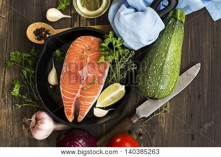 Raw salmon steak in an iron skillet with ingredients for healthy dinner. Top view