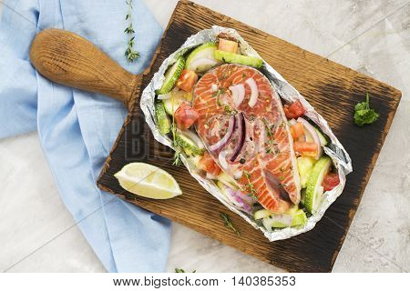 Raw salmon steak with veggies in a foil boat, ready for baking. Copy space
