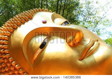 The face of Reclining Buddha image golden exquisite from Thailand.