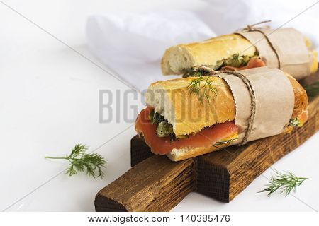 Sandwiches with smoked salmon, potato, pickled cucumbers and dill over white background. Selective focus