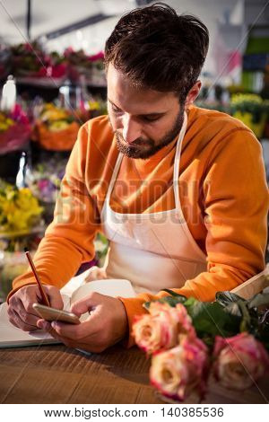 Male florist noting order in dairy from mobile phone