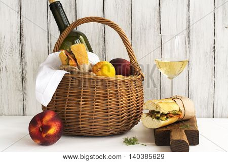 Picnic basket with wine, salmon sandwiches and fruits over white wooden table. Selective focus