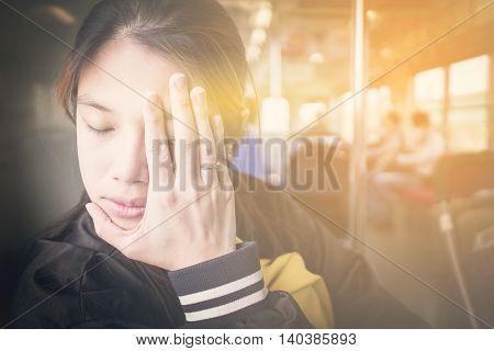Japanese girl having a bad headache on a train. Asian women having a motion sickness on a commute bus.