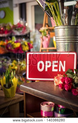 Open signboard on table at flower shop