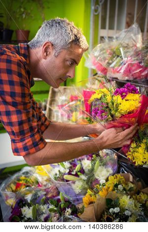 Male florist arranging flower bouquet at his flower shop