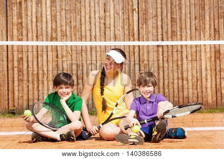 Happy tennis players, young girl and her two brothers, having rest sitting on the clay court after match