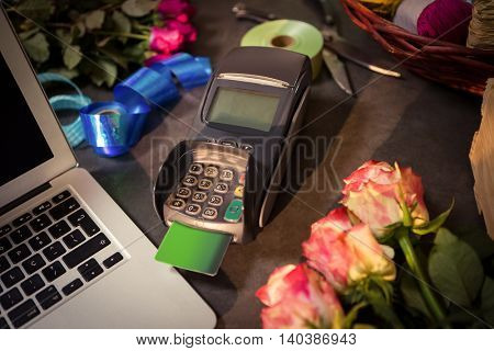 Close-up of laptop and credit card terminal on the table at flower shop