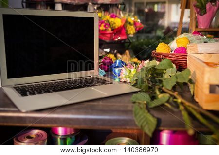 Close-up of laptop and florist supplies on the table at flower shop
