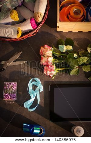 Digital tablet and florist supplies on the table at flower shop