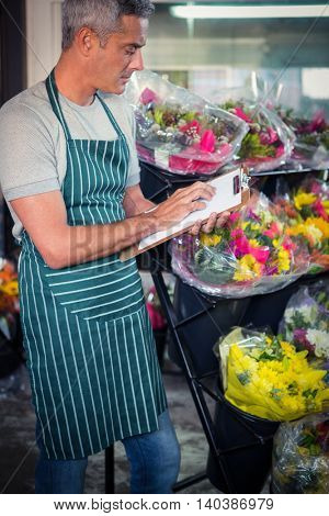 Male florist checking checklist at his flower shop