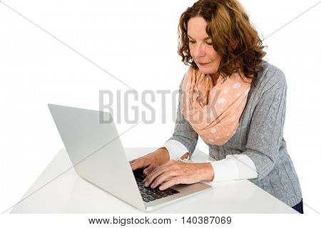 Woman using laptop while standing against white background
