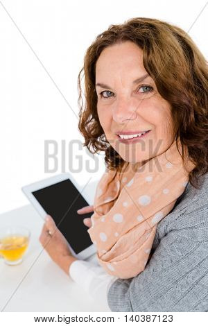 Portrait of cheerful woman using tablet while standing against white background