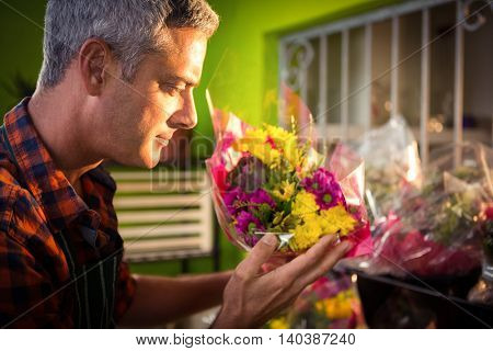 Close-up of male florist smelling flower at his flower shop
