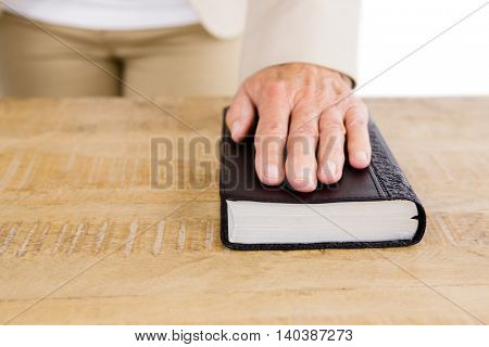 Midsection of woman with hand on bible at table