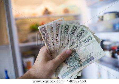 Hand With Pln  Money In Front Of Open Fridge