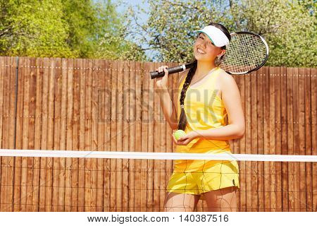 Portrait of happy female tennis player, teenage Asian girl with racket and ball, standing next to the net