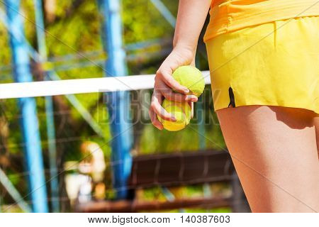 Picture of female tennis player's hand, holding two tennis balls on the court in summer