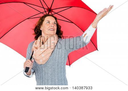 Mature woman holding red umbrella while standing against white background