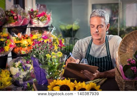 Male florist writing on clipboard at his flower shop