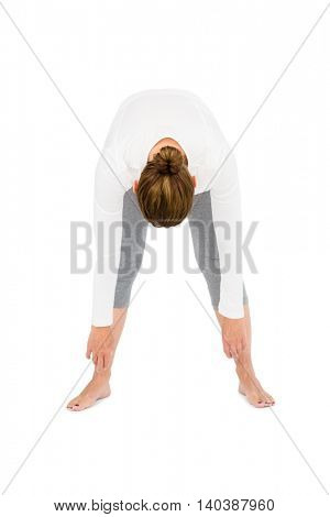 Full length of woman bending while exercising on white background