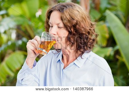 Close-up of mature woman drinking herbal tea
