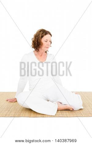 Full length of mature woman exercising against white background