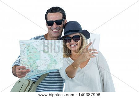 Cheerful mid adult couple taking selfie against white background