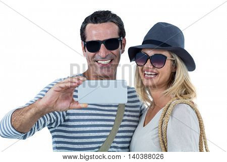 Mid adult couple smiling while taking selfie against white background