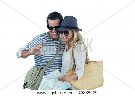 Cheerful couple taking selfie against white background