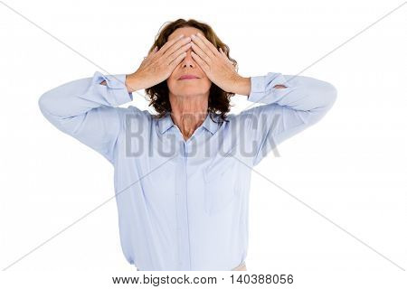 Woman with hands covering eyes against white background