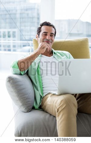 Man smiling while looking in laptop on sofa at home