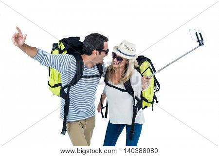 Happy couple taking selfie with monopod against white background