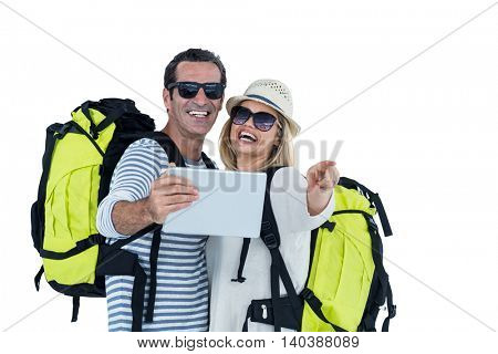 Cheerful couple taking selfie on digital tablet against white background