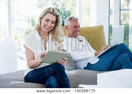 Smiling mature couple using technology while sitting at home