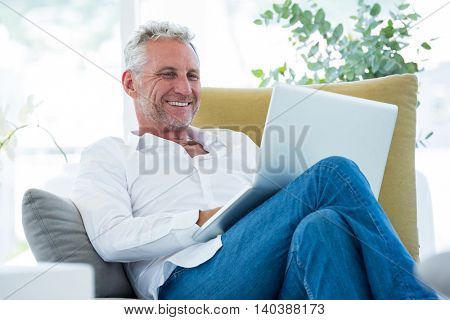 Smiling mature man using laptop while sitting at home