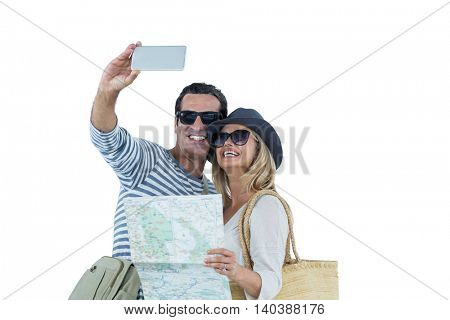 Happy couple with map taking selfie against white background