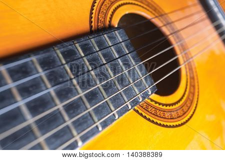 Strings rose and soundboard of a yellow and orange guitar. Musical instrument.