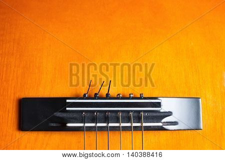 Bridge and strings of a yellow and orange guitar. Musical instrument. Copy space at the top.