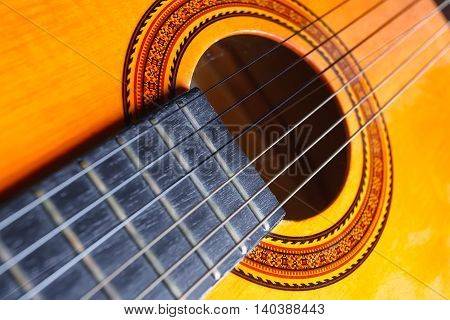 Strings rose and neck of a yellow and orange guitar. Musical instrument.