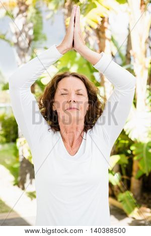Mature woman with eyes closed while practicing yoga