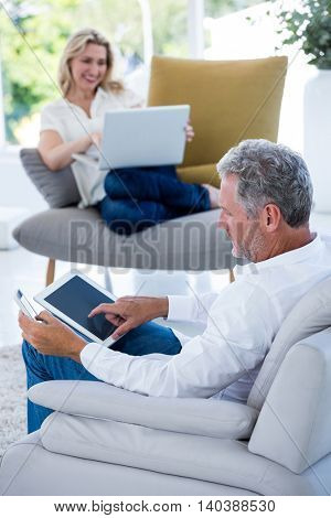 Mature man using tablet while woman holding laptop at home